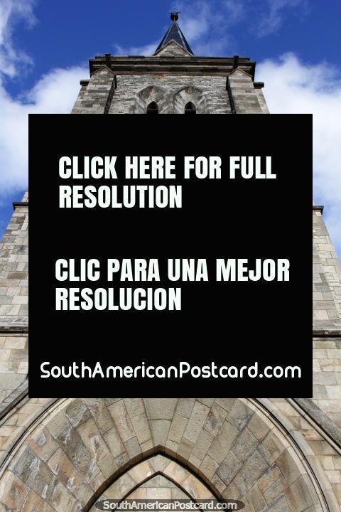 A alta torre de pedra da grande catedral em Bariloche está em um parque de margem de lago. (480x720px). Argentina, América do Sul.