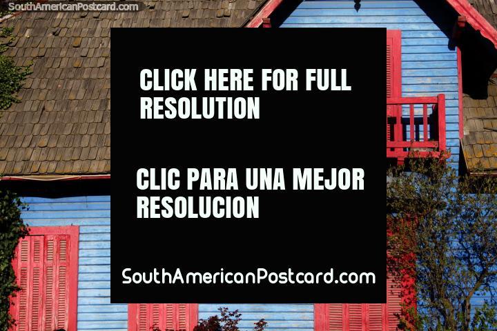 Casa de madeira de azul com balcão vermelho, portas e janelas e um telhado coberto com telhas, em Bariloche. (720x480px). Argentina, América do Sul.