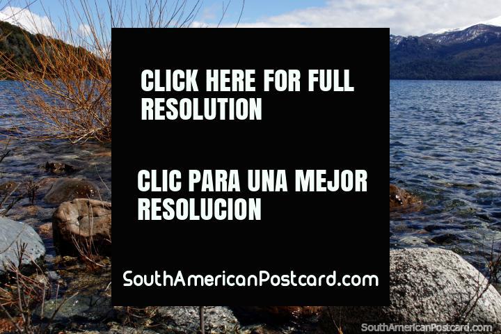 Lago Traful con rocas en el primer plano y montañas nevadas distantes, al norte de Bariloche. (720x480px). Argentina, Sudamerica.
