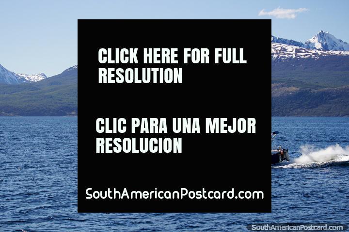 La gente en un bote disfruta de un hermoso día soleado en las aguas de Ushuaia. (720x480px). Argentina, Sudamerica.