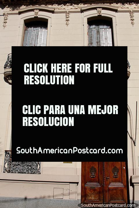 Los balcones de hierro se presentan en esta fachada con una puerta de madera alta en Santa Fe. (480x720px). Argentina, Sudamerica.