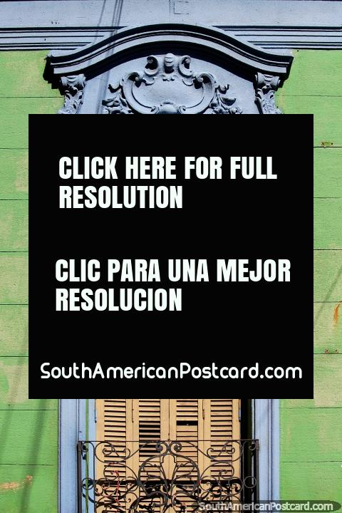 Yellow wooden window shutters surrounded by blue ceramic, a green wooden wall and black iron, house facade in Parana. (480x720px). Argentina, South America.