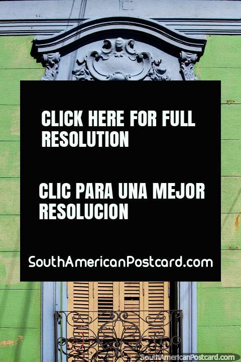 Folhas de janela de janela de madeira amarelas rodeadas de cerâmica azul, uma parede de madeira verde e ferro preto, fachada de casa em Paraná. (480x720px). Argentina, América do Sul.
