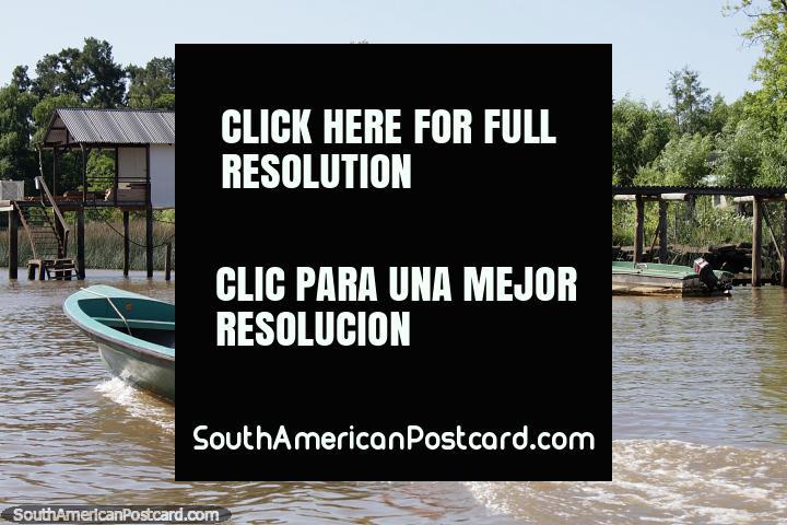 O homem em uma lancha viaja ao longo do rio para além de um molhe de madeira no Tigre, Buenos Aires. (720x480px). Argentina, América do Sul.