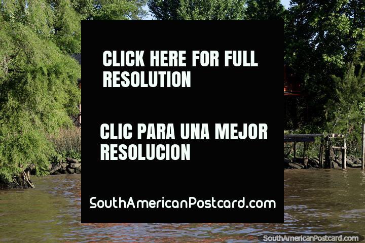 A casa muito tempo vermelha na luz solar em dias termina junto do delta de rio no Tigre, Buenos Aires. (720x480px). Argentina, América do Sul.