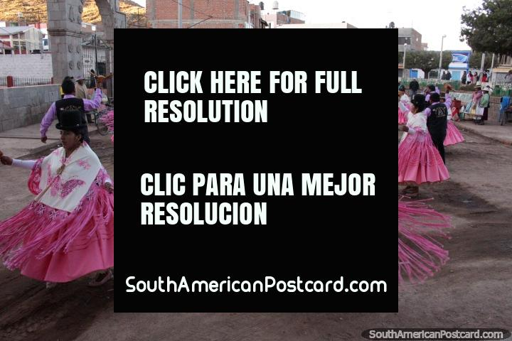 Women in pink and white, men in purple and black, locals dancing in Desaguadero. (720x480px). Bolivia, South America.