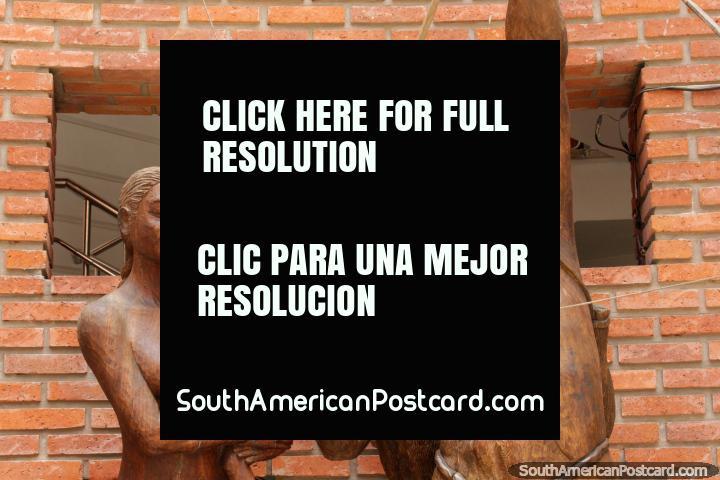 Wooden sculptured family of 3, man shoots a bow and arrow, Santa Cruz. (720x480px). Bolivia, South America.