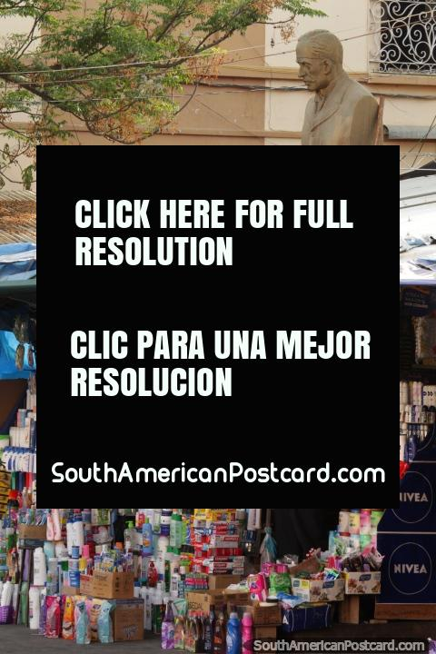 Man sells products on the street below a bust in Tarija. (480x720px). Bolivia, South America.