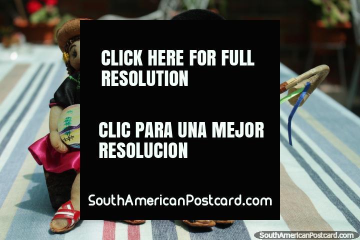 Um par de figuras de boneca que se sentam em um log em Tarija. (720x480px). Bolívia, América do Sul.