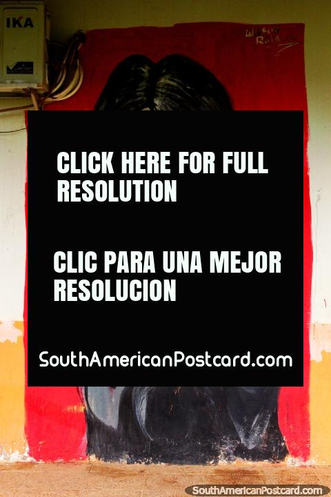 Mujer indígena con rostro pinta un collar de cuentas, arte callejero en Cobija. (480x720px). Bolivia, Sudamerica.