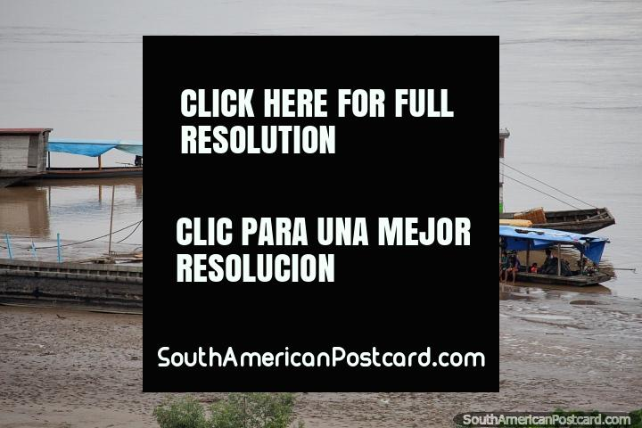 2 level wooden boat and other boats around the wet sands at the port in Riberalta. (720x480px). Bolivia, South America.
