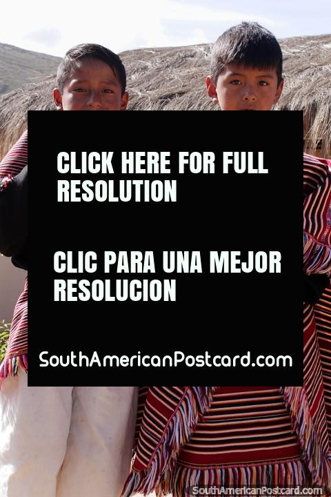 2 boys in traditional clothing blow wooden wind pipes in Puka-Puka. (480x720px). Bolivia, South America.