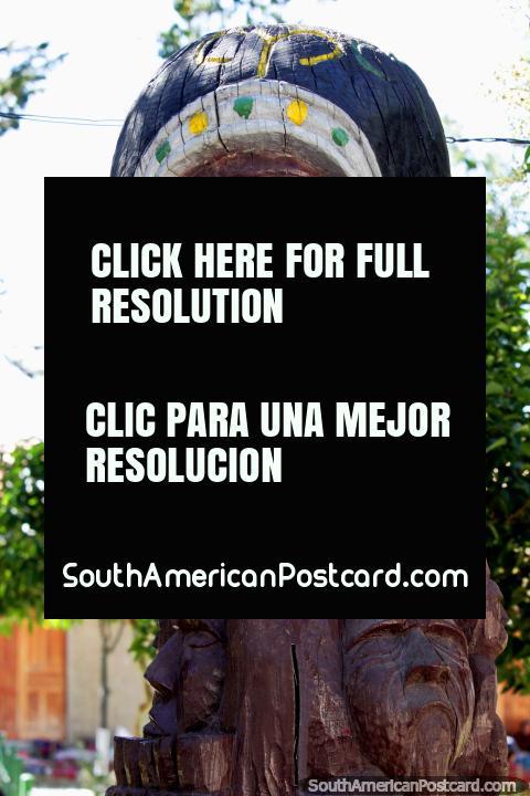 Escultura de madera de una cara grande con 2 abajo en la plaza en Tarabuco. (480x720px). Bolivia, Sudamerica.