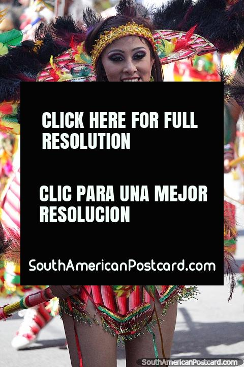 Woman with gold headband, feather earrings, a spear and pink outfit, El Gran Poder in Sucre. (480x720px). Bolivia, South America.