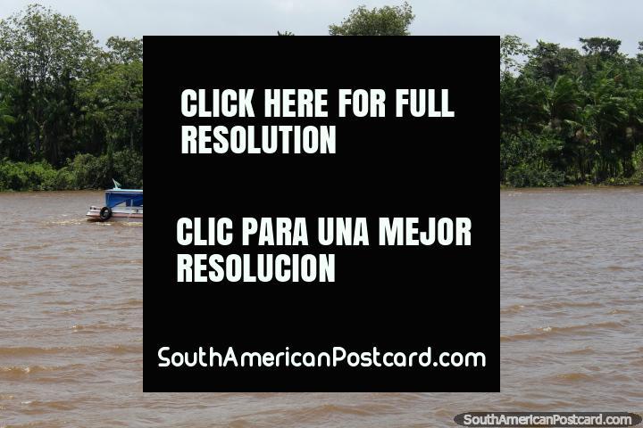 Um pequeno barco de passageiros e uma canoa de rio cruzam caminhos ao oeste de Belém. (720x480px). Brasil, América do Sul.