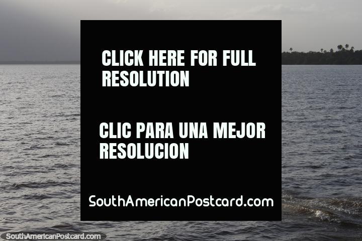 El chico en una canoa dirige hacia el atardecer en el día final en el viaje desde Belem a Macapá. (720x480px). Brasil, Sudamerica.