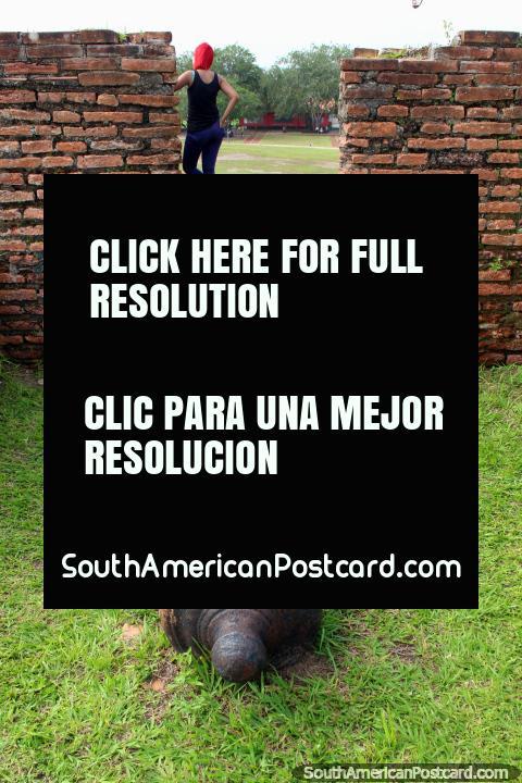 Um canhão aponta para uma menina com o cabelo ruivo tingido no forte Macapa. (480x720px). Brasil, América do Sul.