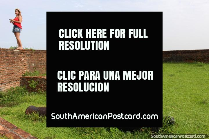 Chica en rojo en una pared de ladrillo y un cañón en la fortaleza en Macapá. (720x480px). Brasil, Sudamerica.
