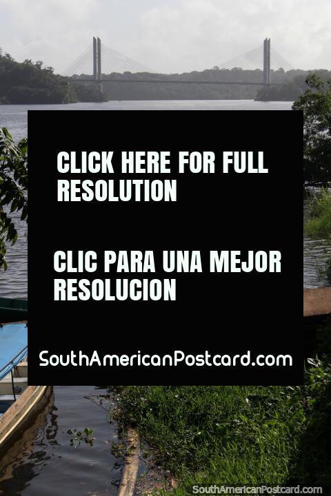 El hombre ata su barco al lado de una rampa en el río en Oiapoque, el puente de la Guayana Francesa en la distancia. (480x720px). Brazil, Sudamerica.