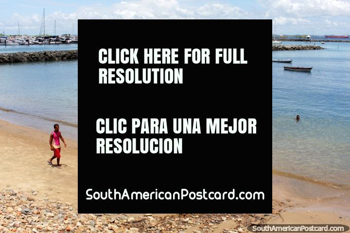 O homem anda ao longo de uma pequena praia, a água parece bastante bonita, o porto de Salvador. (720x480px). Brasil, América do Sul.
