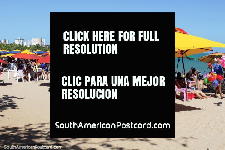 Pessoas que gostam dos seus guarda-chuvas sombreados nas areias de Praia de Pajuçara em Maceio. (720x480px). Brasil, América do Sul.