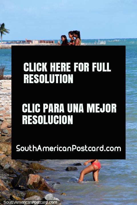 Women enjoying the sun and sea around the rocks at Pajucara Beach in Maceio. (480x720px). Brazil, South America.