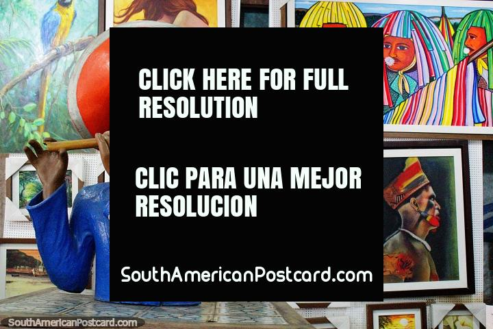 O homem com o chapéu cor-de-laranja toca uma flauta de madeira, pinturas atrás, artes de Olinda. (720x480px). Brasil, América do Sul.