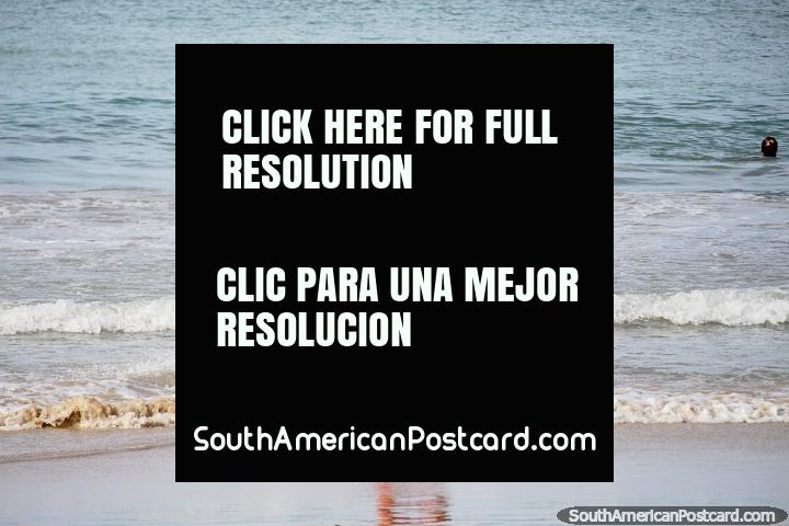 O homem patina ao longo da água em uma tábua de madeira em Praia de Golfinho, Pipa. (720x480px). Brasil, América do Sul.