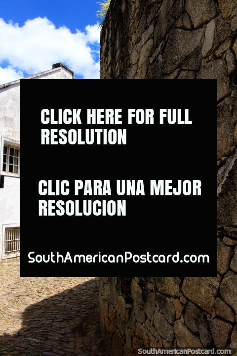 Muro de piedra en la esquina de una calle de adoquines y un edificio blanco en Ouro Preto. (480x720px). Brasil, Sudamerica.
