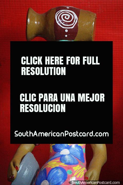 La mujer con un vestido floral rosado y azul tiene una urna en la cabeza, cerámica en Porto Velho. (480x720px). Brasil, Sudamerica.