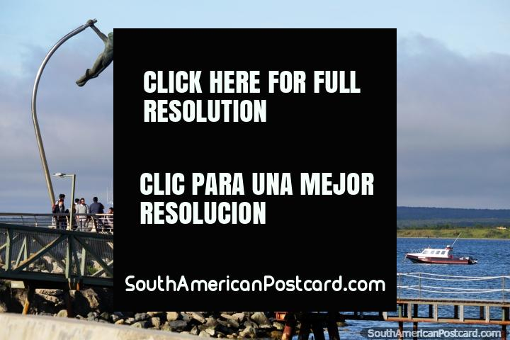 Waterfront and monument in Puerto Natales, a pair of figures take to the sky. (720x480px). Chile, South America.