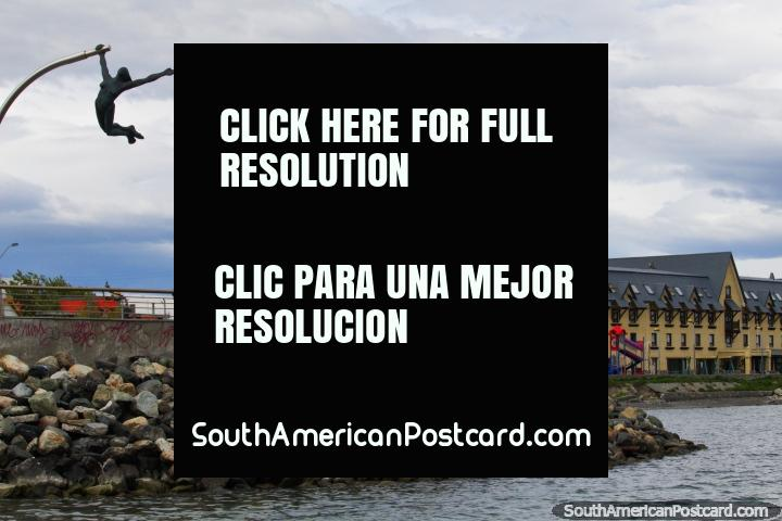 Seafront in Puerto Natales, hotel with a tower, rocks and a monument. (720x480px). Chile, South America.