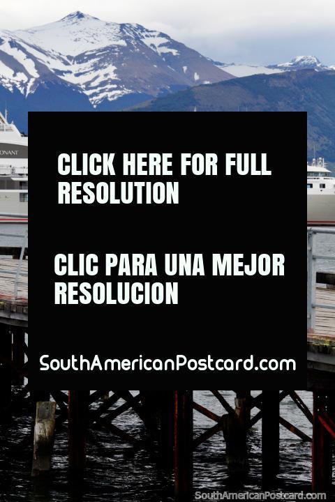 Personas sentadas en el nuevo muelle en Puerto Natales con barco distante y montañas. (480x720px). Chile, Sudamerica.