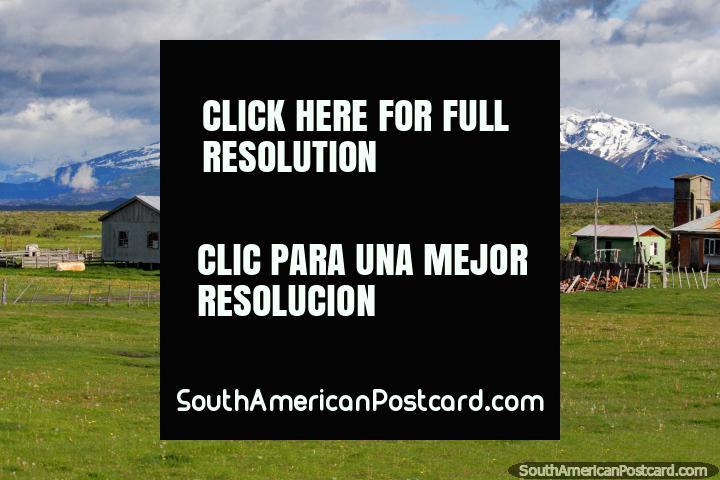 Tierras de labranza, edificios y montañas en el campo entre Puerto Natales y Cerro Castillo. (720x480px). Chile, Sudamerica.
