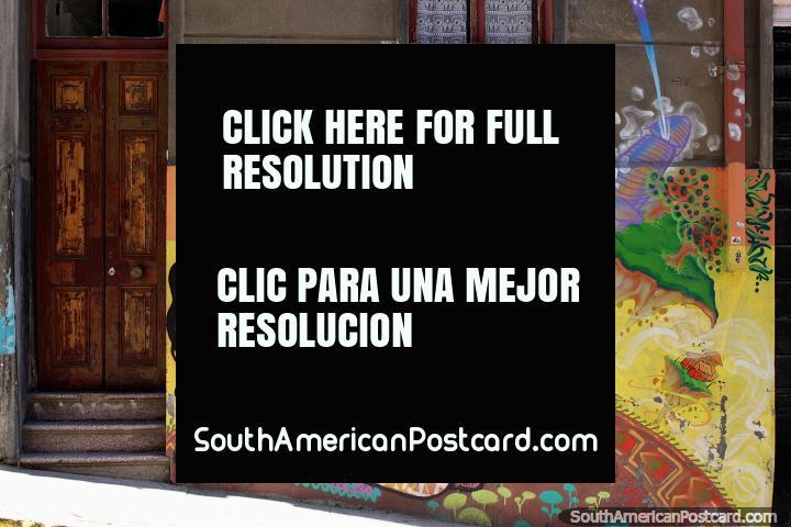 A menina com 3 olhos desenha um quadro e senta-se em um tapete redondo, arte de rua fantástica em Valparaïso. (720x480px). Chile, América do Sul.