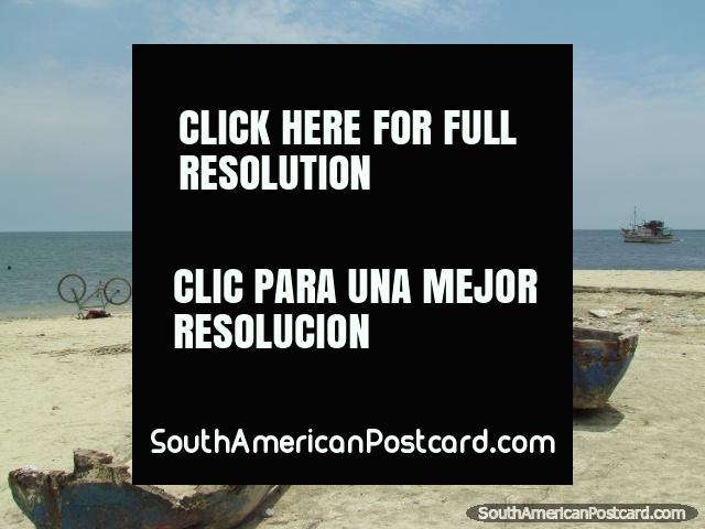 Velhos barcos de madeira e uma bicicleta na praia em Santa Marta. (640x480px). Colômbia, América do Sul.