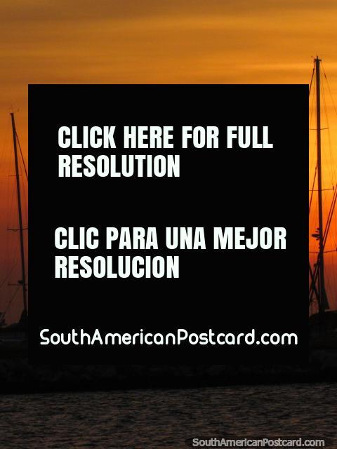 Mastros de veleiros no clube de iate em Santa Marta e um ocaso cor-de-laranja. (480x640px). Colômbia, América do Sul.