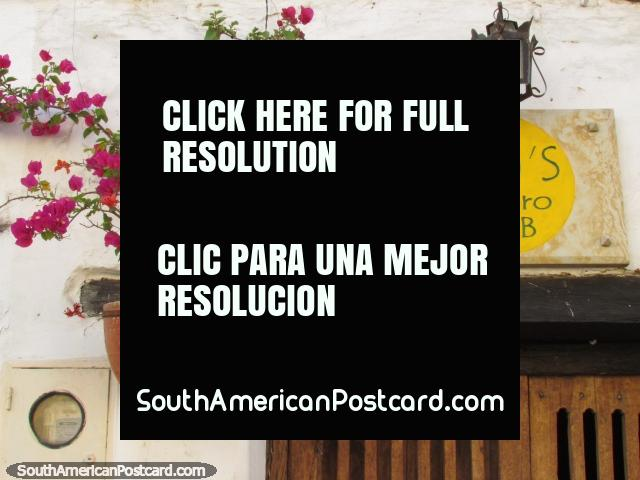 Nice facade of Sam's Gastro Pub in San Gil, pink flowers, wooden door and lamp. (640x480px). Colombia, South America.