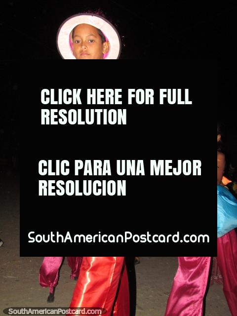 Boy in bright pink and red clothes on stilts at the Taganga carnival. (480x640px). Colombia, South America.