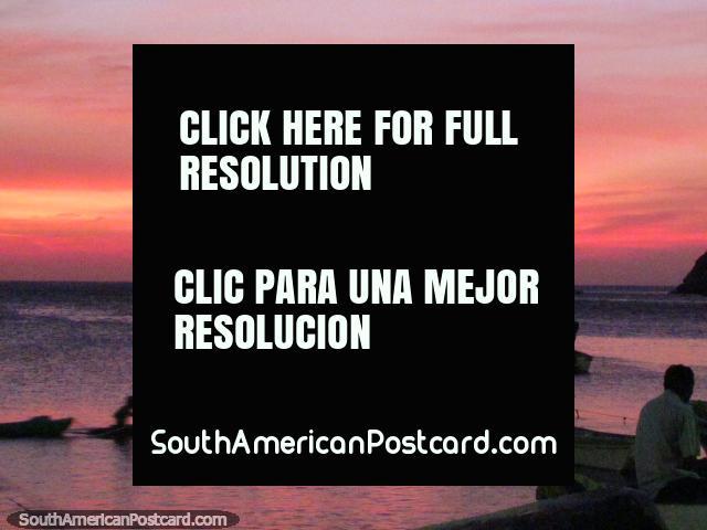 A canoa viaja através de águas rosa e ocaso em Taganga. (640x480px). Colômbia, América do Sul.