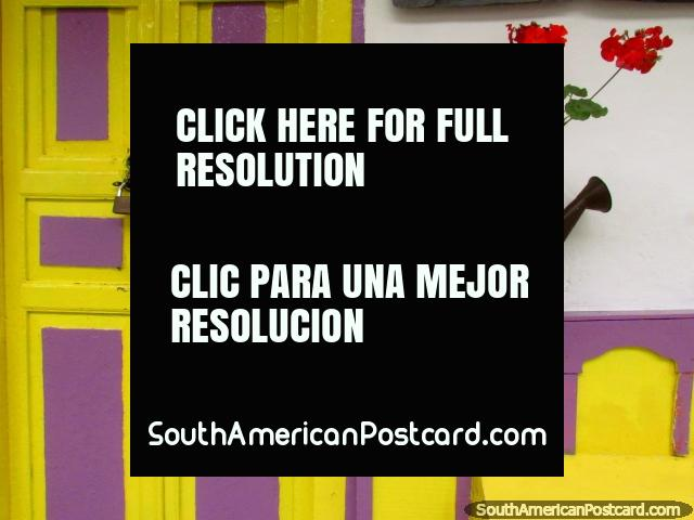 Yellow and purple facade with a watering can and red flowers in Salento. (640x480px). Colombia, South America.