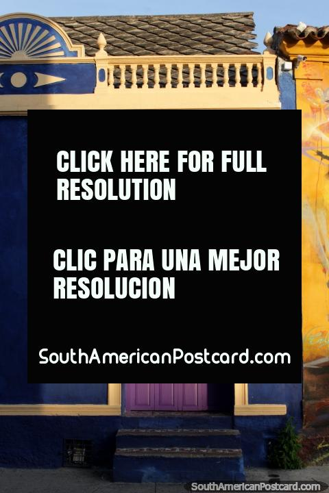 Fachada azul com uma porta purpúrea arcada, pequena casa bonita em Cartagena. (480x720px). Colômbia, América do Sul.