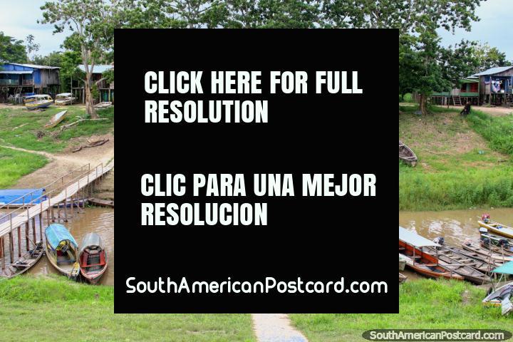 Canoas de rio de madeira, uma ponte de madeira e casas de madeira em pernas de pau, o Amazônia em Leticia. (720x480px). Colômbia, América do Sul.