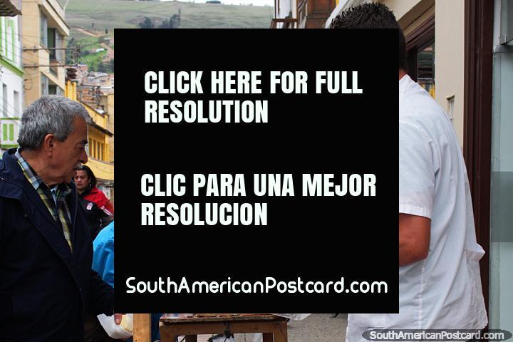 O homem massageia um caramelo gooey regalo saboroso de pôr em xïcaras, para a venda em Tunja. (720x480px). Colômbia, América do Sul.