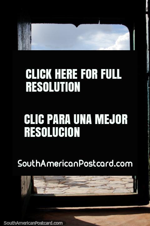 Da porta de igreja que olha para fora a enorme praça pública em Villa de Leyva. (480x720px). Colômbia, América do Sul.