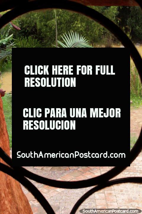 Palmera y estanque, vista a través de una ventana en la Casa Terracota en Villa de Leyva. (480x720px). Colombia, Sudamerica.