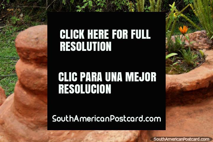 Maniquí de cerámica que miente en el césped, visión desde un patio en la Casa Terracota en Villa de Leyva. (720x480px). Colombia, Sudamerica.