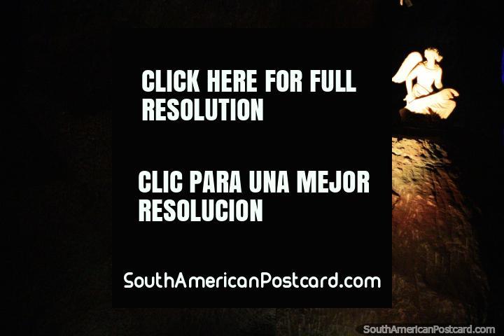 Anjo branco incandescente que se senta em cima de uma rocha no fim do túnel de cruzes, a Catedral de Sal, Zipaquira. (720x480px). Colômbia, América do Sul.