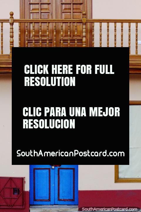Colorful blue door and natural wooden balcony and door above in Zipaquira. (480x720px). Colombia, South America.