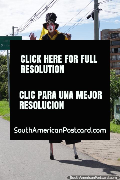 Man on stilts wearing makeup, standing on the roadside waving a flag in Girardot. (480x720px). Colombia, South America.